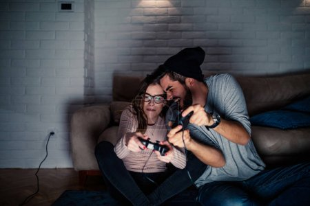 Photo for Photo of young couple competing while playing video games at home. - Royalty Free Image