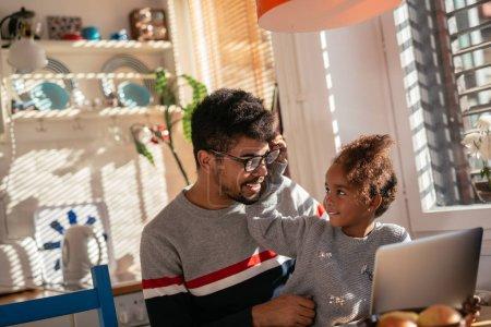 Photo pour Photo de la fille noire assise sur les genoux du père et tenant ses lunettes tout en travaillant à la maison . - image libre de droit