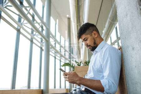 Shot of an african american business man using mobile phone in the company.