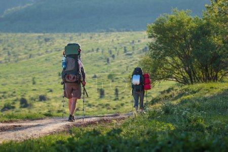 Photo pour Touristes avec sacs à dos randonnée dans les montagnes - image libre de droit