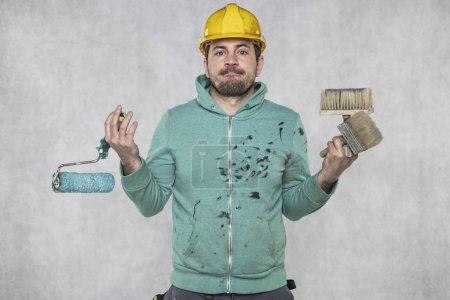 Photo pour Le peintre ne sait pas quels outils de peinture choisir pour le travail - image libre de droit