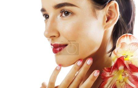 Photo pour Jeune jolie brune vraie femme à fleur rouge amaryllis gros plan isolé sur fond blanc. Maquillage fantaisie mode, rouge à lèvres lumineux, ongles créatifs Ombre manucurés - image libre de droit