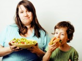 mature woman holding salad and little cute boy with hamburger te
