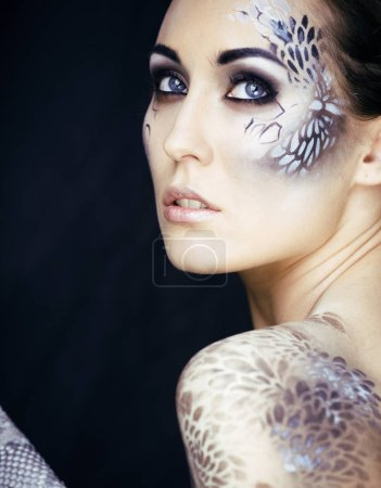 fashion portrait of pretty young woman with creative makeup like