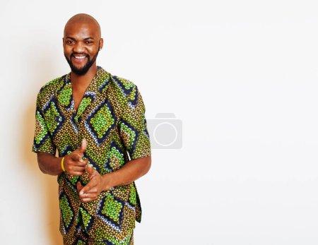 Photo pour Portrait de jeune homme africain beau portant un costume national vert vif geste souriant, des trucs de divertissement de près - image libre de droit