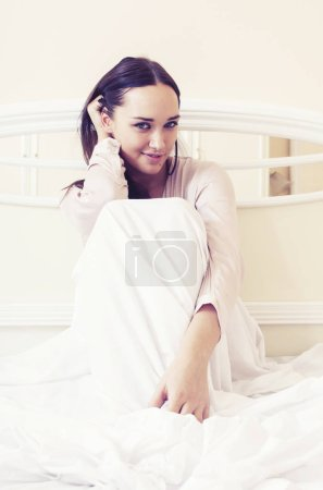 young pretty brunette woman laying in bed, luxury white interior