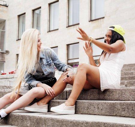 Deux adolescentes en face du bâtiment souriant, ayant de l'Université