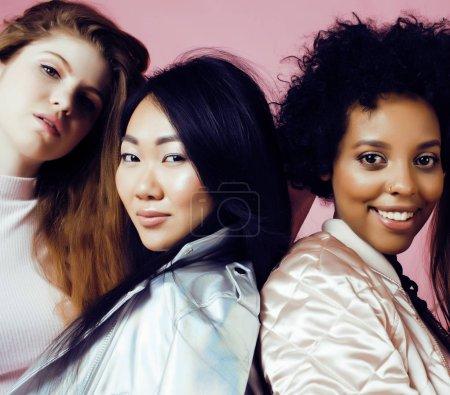 Photo pour Trois filles de différents pays avec apromotion dans la peau, des cheveux. Asiatiques, scandinaves, afro-américaine bonne humeur émotionnelle posant sur fond rose, célébration de la journée femme, concept de gens lifestyle bouchent - image libre de droit