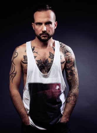 Photo for A man with tattooes on his arms. Silhouette of muscular body. caucasian brutal hipster guy with modern haircut, looking like criminal close up - Royalty Free Image