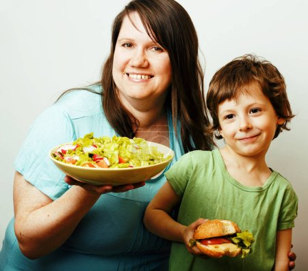 Photo for Mature woman holding salad and little cute boy with hamburger teasing close up, family unhealthy food - Royalty Free Image