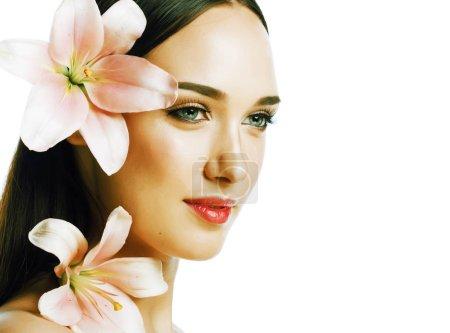 Photo pour Jeune jolie dame gros plan avec les mains sur le visage isolé fleur lis brunette spa nu maquillage macro - image libre de droit