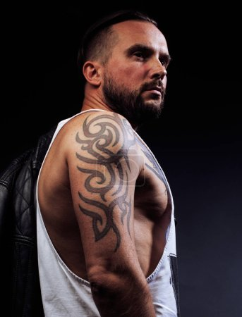 A man with tattooes on his arms. Silhouette of muscular body. ca