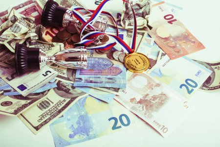 Sport winning concept: three cups among diverse currencies euro,