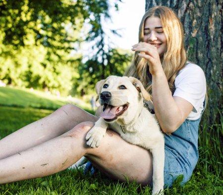 Foto de Joven atractivo rubia real gorda jugando con su perro en el parque verde en verano, el concepto de pueblo de estilo de vida - Imagen libre de derechos