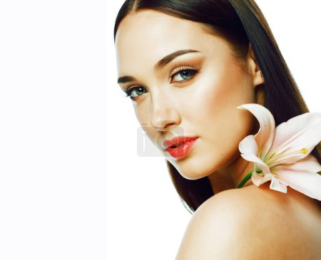Photo for Young attractive lady close up with hands on face isolated flower lily brunette spa nude makeup macro - Royalty Free Image