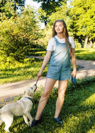 Photo for Young attractive blond real fat woman playing with her dog in green park at summer, lifestyle people concept - Royalty Free Image