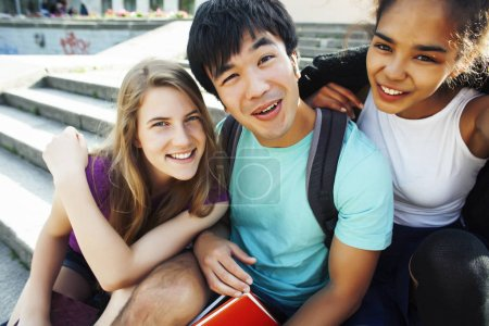 Photo pour Joli groupe de teenages dans le bâtiment de l'université avec les livres huggings, diversité des nations étudiants réelle de vie - image libre de droit