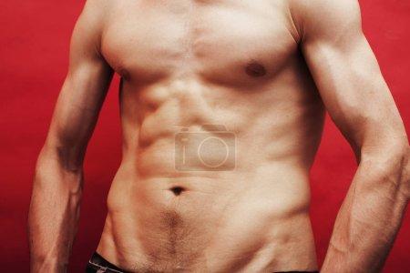Photo pour Homme restant abc nu de torse sur le fond rouge, plan rapproché de sport de mode de vie - image libre de droit