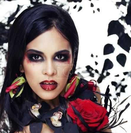 Photo pour Jolie femme brune avec des bijoux roses, noir et rouge, lumineux maquillage kike un vampire gros plan lèvres rouges, concept halloween - image libre de droit