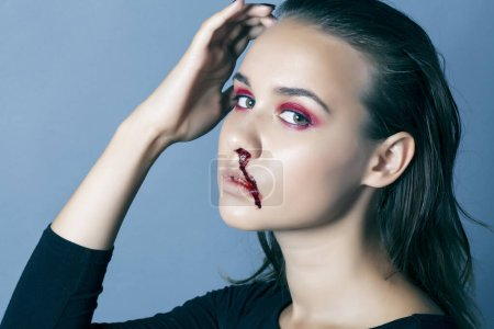Photo for Young pretty woman with blood from her nose closeup fashion makeup on halloween celebration, people abuse concept closeup - Royalty Free Image