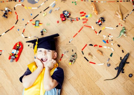 Photo for Little cute preschooler boy playing toys at home happy smiling in graduation hat, lifestyle children , world map with pieces, self education concept - Royalty Free Image