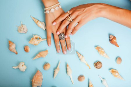 beautiful woman hands with pink manicure holding sea shells, lot of rings on fingers on blue background, luxury jewelry concept