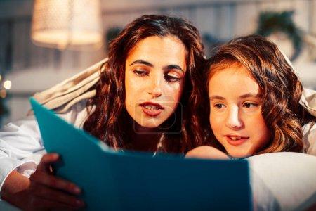 Photo pour Jeunes jolies filles au lit à la messe de Noël matin, heureux style de vie souriant de la famille au livre de lecture de vacances gros plan - image libre de droit