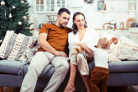 Photo pour Jeune famille heureuse à la maison en autocar en attente de la messe de Noël avec arbre décoré, style de vie personnes au concept de vacances gros plan - image libre de droit