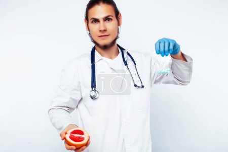 Photo for Young pretty doctor with stethoscope holding fruits, healthy food care concept closeup - Royalty Free Image