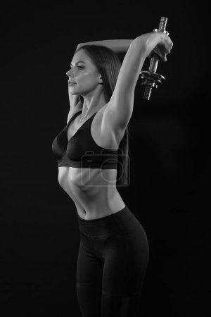Photo for Fitness woman in sportswear doing exercises with dumbells. - Royalty Free Image