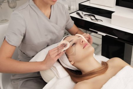 Photo for Facial treatment of a young woman in a cosmetology salon - Royalty Free Image
