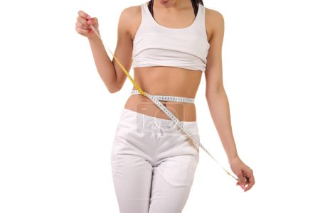 Photo for Young girl with a thin waist makes measuring tape - Royalty Free Image