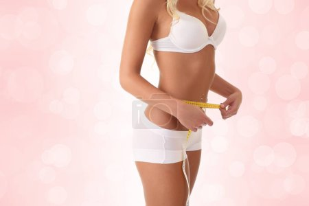Photo for Woman measuring her slim body in white linen - Royalty Free Image
