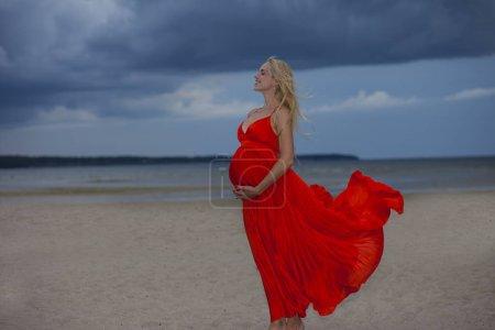 Photo pour Jeune fille positive dans une robe lumineuse rouge sur un fond de paysage nuageux - image libre de droit