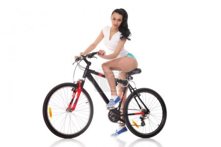 Photo for Sexy fitness.Young seductive woman in sport wear posing on the bicycle - Royalty Free Image
