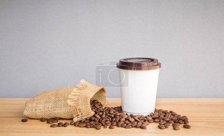 Photo pour Livre blanc café tasse à café en grains sur le bureau en bois - image libre de droit
