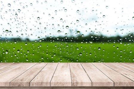 Foto de Suelo de madera con tablones y clima lluvioso sobre fondo con gotas de agua sobre vidrio - Imagen libre de derechos