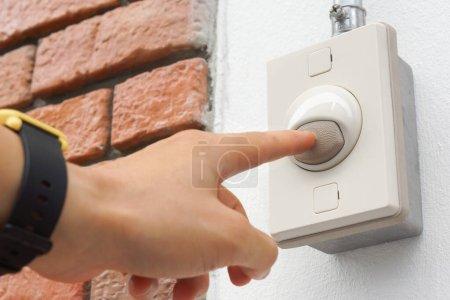 Hand drückt auf Türklingelschalter an der Wand