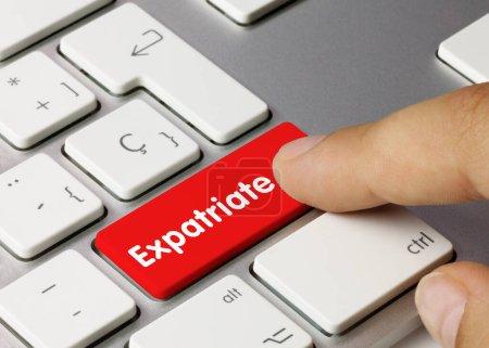 Photo pour Expatrié écrit sur Red Key of Metallic Keyboard. Touche de pression des doigts. - image libre de droit