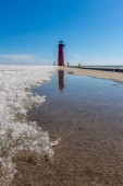 Reflections of the Kenosha north pierhead lighthouse in the ice melt off. Late winter/early spring, Kenosha, Wi.