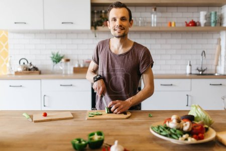 Photo for Picture of man cooking vegetables on table in kitchen - Royalty Free Image