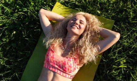 Photo pour Photo de jeune femme bouclée dans des lunettes de soleil couchée sur le tapis dans le parc le jour de l'été - image libre de droit