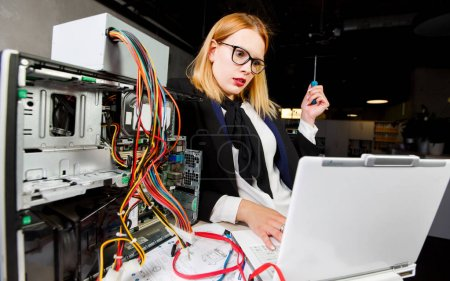 Photo for Photo of woman in glasses at table with broken processor and laptop in office - Royalty Free Image