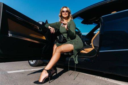 Photo pour Image de femmes blondes heureuses avec des clés en robe longue assis dans la voiture avec porte ouverte dans l'après-midi - image libre de droit
