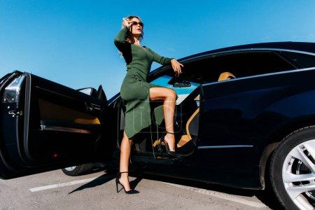 Photo pour Photo de blonde sexy avec des clés en lunettes de soleil en robe longue debout près de voiture noire avec porte ouverte dans l'après-midi - image libre de droit