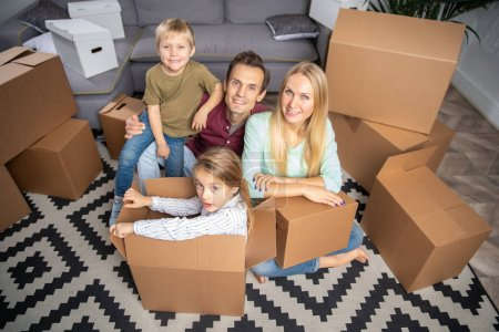 Photo for Photo from above young parents and children among cardboard boxes sitting on floor in new apartment - Royalty Free Image