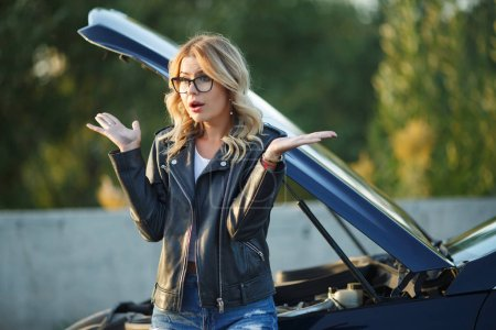 Photo pour Photo de femme frustrée dans une voiture cassée avec capot ouvert pendant la journée - image libre de droit