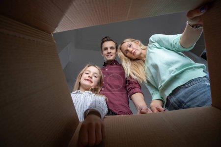 Photo pour Photo des parents et la fille à la recherche à l'intérieur de la boîte en carton dans l'appartement - image libre de droit