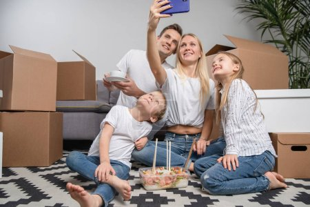 Photo pour Photo de l'homme, des enfants et des femmes prenant selfie assis sur le sol parmi des boîtes en carton dans un nouvel appartement - image libre de droit