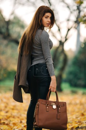 Photo for Full-length photo from back of long-haired woman in sunglasses with bag in her hand against background of autumn forest at day - Royalty Free Image